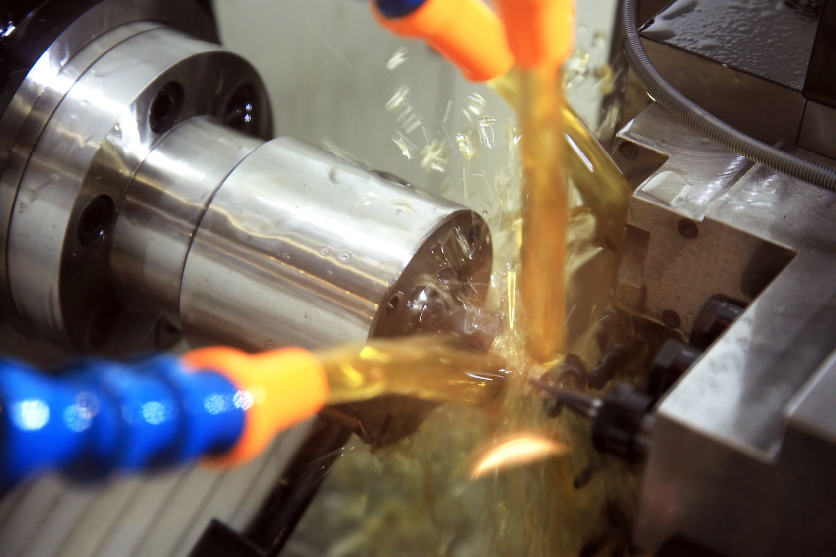 metal blank machining process on lathe with cutting tool and coolant at steel manufacturing